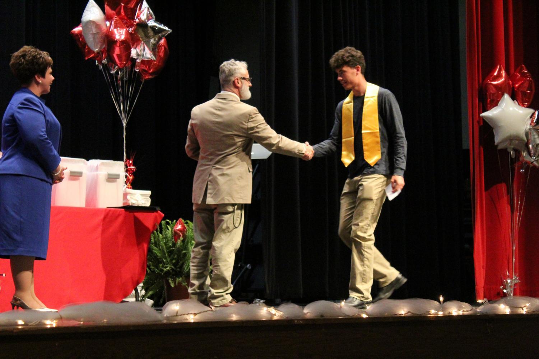 Principle Bill Ferrar shakes senior scholar Craig Latty's hand. Latty was also honored with Summa Cum Laude, Top 100, CTE Completer-Engineering, and CTE Completer - Arch Design.