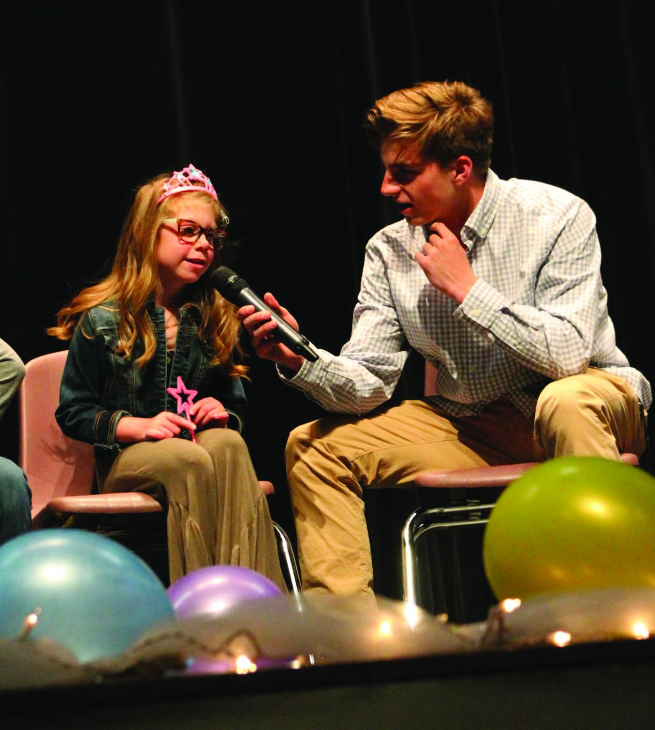 Sophomore Mitchell Meier asks Kelsie questions during the Wish Week assembly. MHS raised $3,013 dollars for her wish.