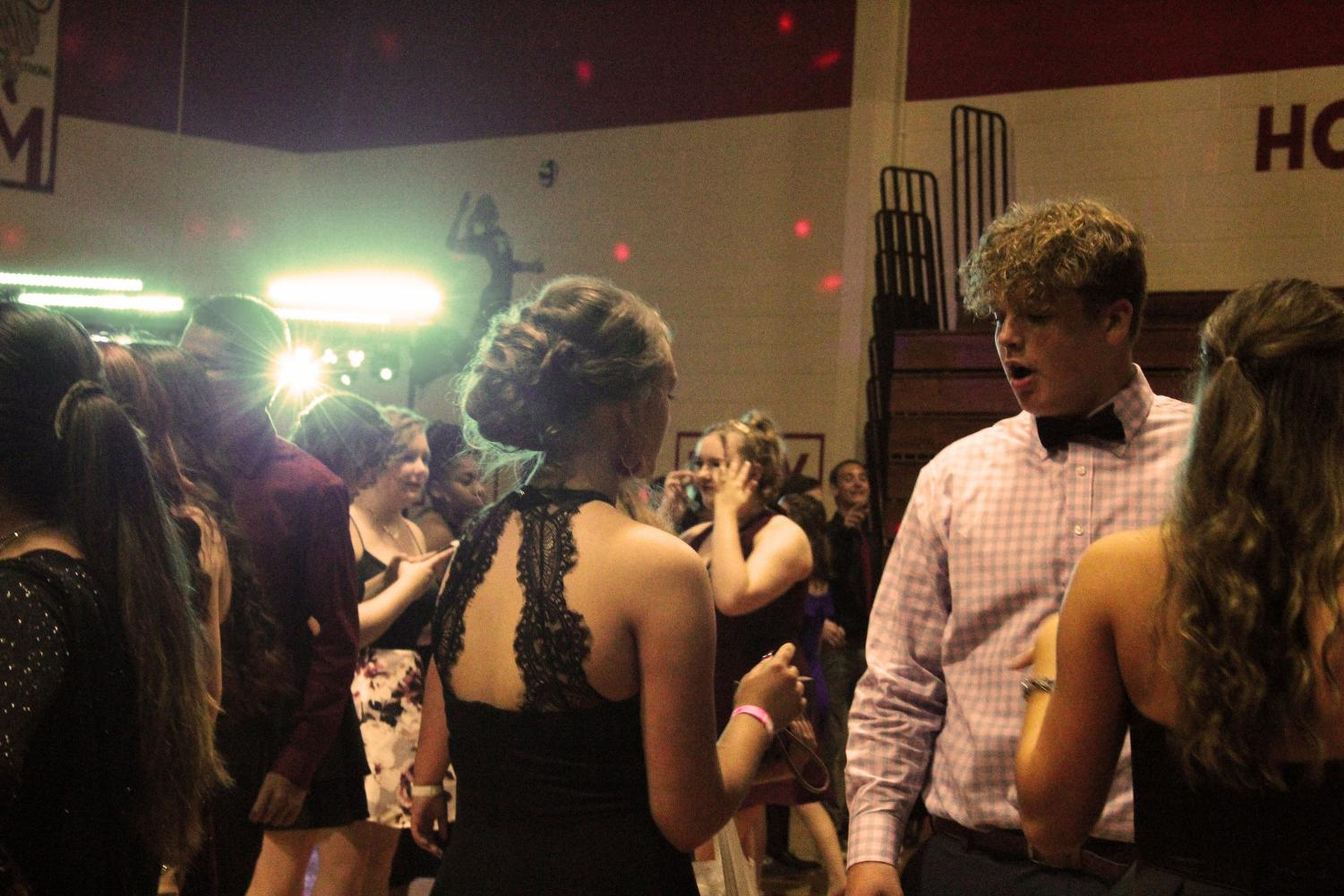 Sophomore Jordan Bassler talks with friends at the homecoming dance last Saturday.  The security system installed last summer left the dance lit brighter than usual.