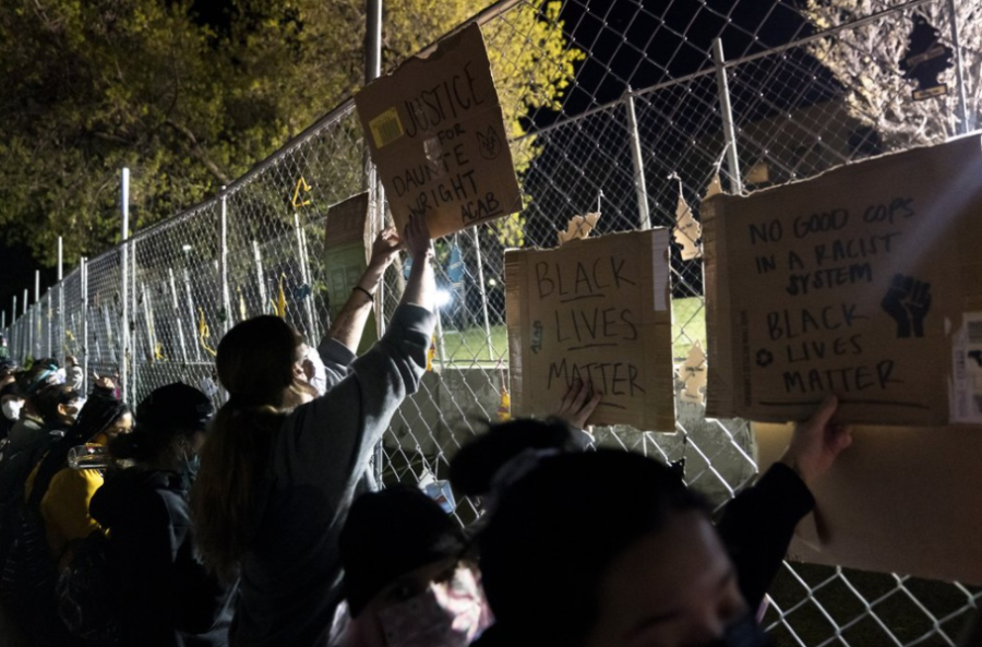 From AP News: Demonstrators press against a security fence at the Brooklyn Park Police Department on April 16.